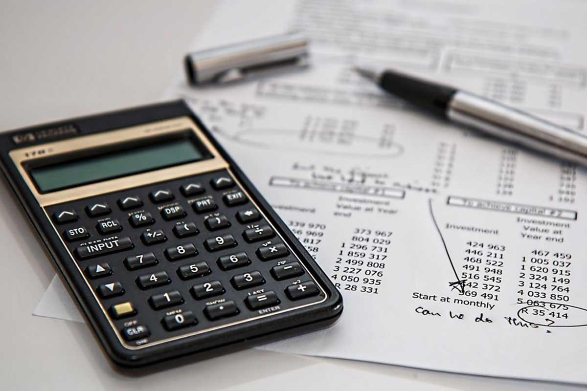 calculator, pen and report